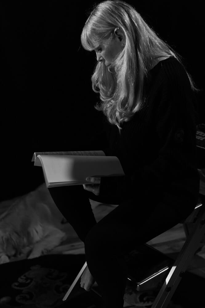 Black and white photo of Sssh founder Angie Rowntree sitting on ladder and reading book