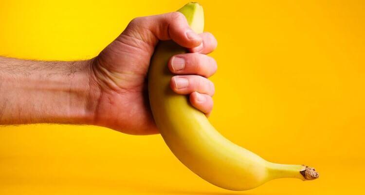 Screeshot of male hand stroking a banana to represent male handjob. Yellow background.